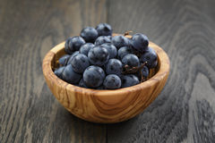 Ripe isabella grapes in wood bowl on table Royalty Free Stock Photo