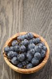 Ripe isabella grapes in wood bowl on table Stock Images