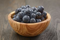 Ripe isabella grapes in wood bowl on table Stock Image