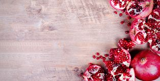 Ripe juice pomegranate fruit on black background - whole and cut, top view. Banner royalty free stock images