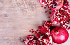 Ripe juice pomegranate fruit on black background - whole and cut, top view. royalty free stock image