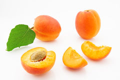 Ripe, juicy and appetizing apricot fruits with green leaves. Isolated on white background Royalty Free Stock Photography
