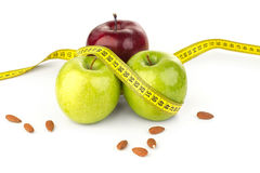 Ripe juicy apples, almonds, and tape measure. On a white background Stock Photography
