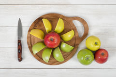 Ripe juicy apples lie on wooden board with a knife next to it in top view royalty free stock photography