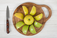 Ripe juicy apples lie on wooden board with a knife next to it in top view royalty free stock image