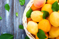 Ripe juicy apricots. In a basket on a wooden background Stock Photo