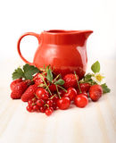 Ripe juicy berries and jug on the table Royalty Free Stock Photos