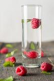 Ripe juicy berries of raspberries in a glass beaker. Fresh green mint leaves. Copy space Royalty Free Stock Image