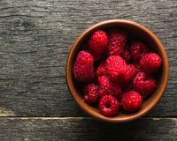 Ripe juicy berries of raspberry and clay bowl. View from above. Royalty Free Stock Images