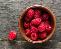 Ripe juicy berries of raspberry and clay bowl. View from above. Stock Image