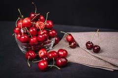 Ripe juicy cherries in a glass on a dark background. Ripe juicy cherries in a glass Stock Image