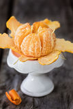 Ripe and juicy clementine. Peeled mandarin on small white stand Royalty Free Stock Photos