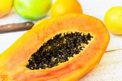 Ripe juicy cut in half papaya raw citrus fruits orange lemon green apples on white wood kitchen table. Healthy lifestyle. Plant based vegan diet concept. Summer royalty free stock photography