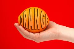 Ripe juicy delicious orange in hand isolated on red background. Healthy eating and dieting concept. Word ORANGE royalty free illustration