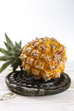 Ripe juicy fresh baby pineapple on black stone Royalty Free Stock Photos