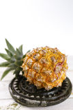 Ripe juicy fresh baby pineapple on black stone Stock Photos