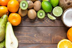 Ripe fruit pear kiwi lime mandarin orange coconut on a wooden table with place for inscription. Ripe juicy fruit pear kiwi orange mandarin orange lime coconut Stock Photography
