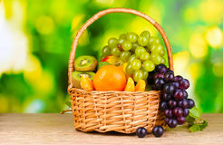 Ripe juicy fruits in basket on wooden table Royalty Free Stock Photos