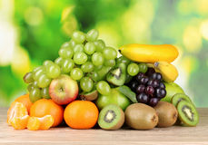 Ripe juicy fruits on wooden table on green Stock Image