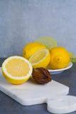 Ripe juicy lemons witn juicer stick made from olive tree wood Stock Photo