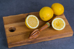 Ripe juicy lemons witn juicer stick made from olive tree wood Stock Images