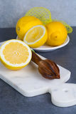 Ripe juicy lemons witn juicer stick made from olive tree wood Royalty Free Stock Photography