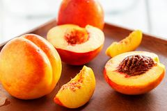 Ripe juicy Nectarines organic fruits whole and slice on wooden background. Selective focus. Toned photo stock photography