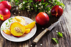 Ripe juicy nectarines. In a plate on the old wooden background. health and diet concept Stock Photos