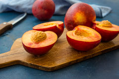 Ripe juicy nectarines, whole and halved on wood cutting board, knife, blue kitchen towel, close up Royalty Free Stock Photo