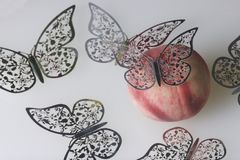 A ripe juicy peach lies on a white surface. All around is decorated with butterflies cut from foil. A ripe juicy peach lies on a white surface. All around is Stock Photo