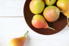 Ripe juicy pear and a clay plate Stock Photos