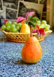 A ripe juicy pear lies on a table, in the background a vase with grapes and pears royalty free stock image