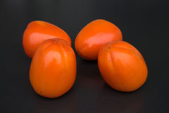 Ripe juicy persimmons on a dark background fresh fruits Royalty Free Stock Image