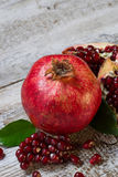 Ripe juicy pomegranate on wooden table Stock Photos