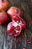 Ripe juicy pomegranates on dark table Stock Photography
