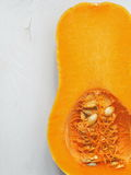 Ripe juicy pumpkin. Butternut squash upon old wooden background. Ripe juicy pumpkin. Butternut squash upon old wooden background, halved. Copy space for your Stock Image