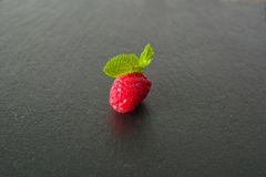 Ripe juicy raspberries on a dark background. Fresh green mint leaves. View from above Royalty Free Stock Photography