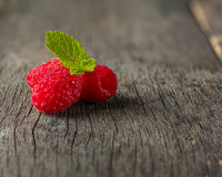 Ripe juicy raspberries on a dark background. Fresh green mint leaves. Stock Photography
