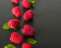 Ripe juicy raspberries on a dark background. Fresh green mint leaves. Royalty Free Stock Photography