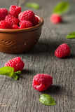 Ripe juicy raspberries on a dark background. Fresh green mint leaves. View from above Stock Photo
