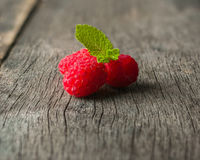 Ripe juicy raspberries on a dark background. Fresh green mint leaves. Stock Images