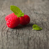 Ripe juicy raspberries on a dark background. Fresh green mint leaves. View from above Stock Images