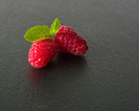 Ripe juicy raspberries on a dark background. Fresh green mint leaves. Royalty Free Stock Images