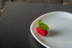 Ripe juicy raspberries on a plate on dark background. Fresh green mint leaves. Stock Photography