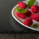 Ripe juicy raspberries on a plate on dark background. Fresh green mint leaves. Royalty Free Stock Photography