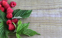 Ripe juicy raspberries on a wooden background. Fresh green leaf. The view from the top. With place for text Stock Photography