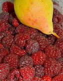 Ripe juicy raspberry and aromatic pear, autumn delicacies royalty free stock images
