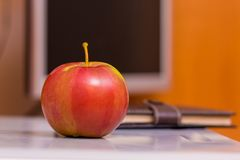 Ripe juicy red apple on the background of the computer. Useful f royalty free stock photos