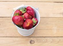Ripe juicy red strawberries are in a white metal bucket on woode Stock Photos