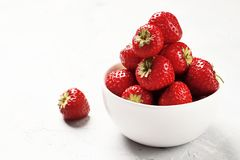 Ripe juicy strawberries in a bowl on a light background stock images